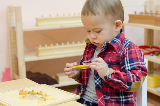 Cute little boy in the classroom early development. Montessori education.