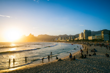 Golden sun setting behind the silhouette of Two Brothers Mountain against the curve of Ipanema Beach at Arpoador in Rio de Janeiro, Brazil