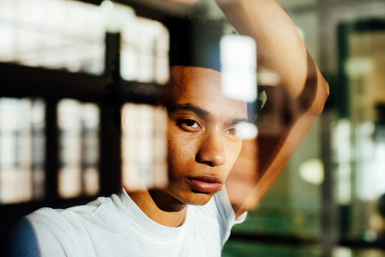 Portrait of a young man standing by the window and looking out with no expression