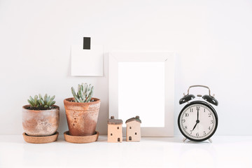 Succulents or cactus in clay pots over white background on the table with the clock and picture frame.
