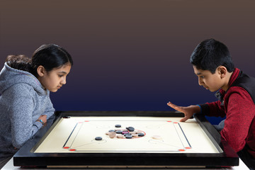 Indian Siblings Playing Carrom on the Carrom Board