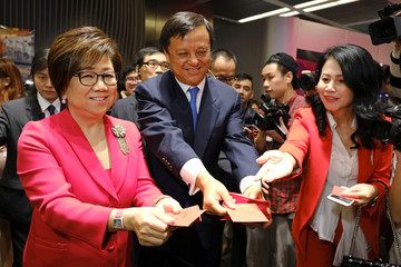 Hong Kong Exchanges and Clearing Ltd (HKEX) chairman Laura Cha Shih May-lung and Chief executive Charles Li Xiaojia distribute red packets during a ceremony marking the first day of trade after Lunar New Year at the Hong Kong stock exchange in Hong Kong