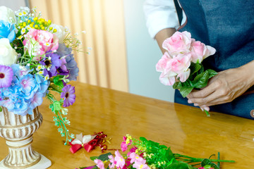 lower artist woman working to decorate  artificial flowers