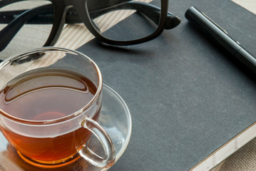 One glass pen, notebook, glasses and tea