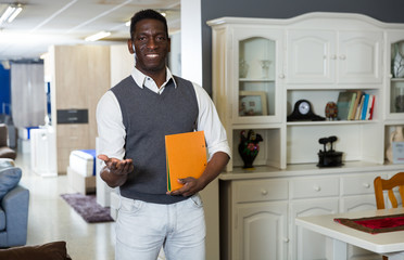 Portrait of seller man who is holding folder with prices for modern furniture