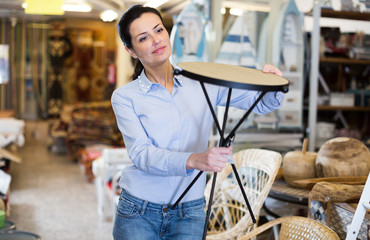 Smiling female holding chair before buying at store