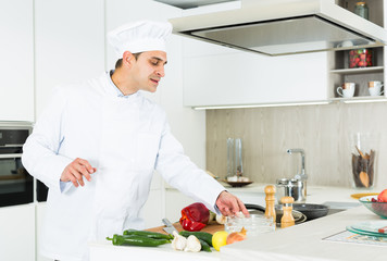 Male cook is making salad on his work place in the kitchen