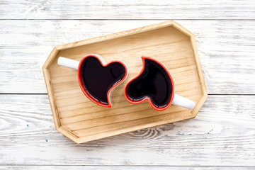 Heart-shaped mugs for Valentine's day on white wooden background top view copy space