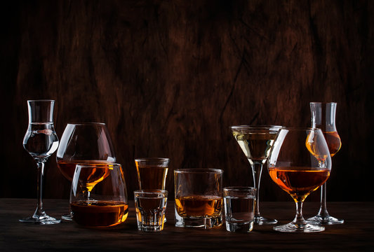 Selection of hard strong alcoholic drinks in big glasses and small shot glass in assortent: vodka, cognac, tequila, brandy and whiskey, grappa, liqueur, vermouth, tincture, rum.