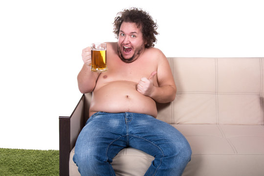 Funny fat man drinking beer at home.
