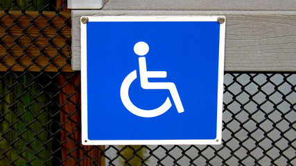 Handicap square metal sign, blue and white attached a metal fence