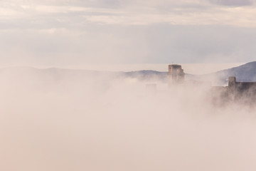 A view of Rocca Maggiore castle in Assisi (Umbria, Italy) in the middle of fog