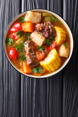 Sancochois a meats and vegetables stew, enjoyed in Latin America and the Spanish Caribbean islands close-up on a bowl. Vertical top view
