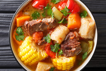 Sancocho Recipe a hearty and absolutely delicious stew made with meat, vegetables and spice close-up on a plate. horizontal top view
