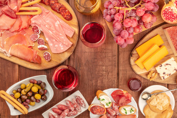 Gourmet Charcuterie. Various sausages and hams, deli meats, and a cheese platter, shot from the top on a dark rustic background with wine, olives and copy space