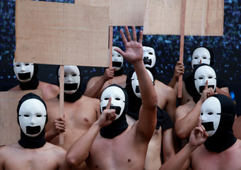 """Naked members of a university fraternity gesture and carry blank placards to call for freedom of expression during the annual """"Oblation Run"""" at the University of the Philippines, in Quezon City"""