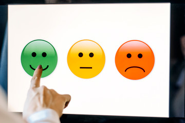 hand shows on green round smiley face on black monitor