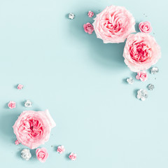 Flowers composition. Frame made of rose flowers on pastel blue background. Valentines day, mothers day, womens day, spring concept. Flat lay, top view, copy space, square