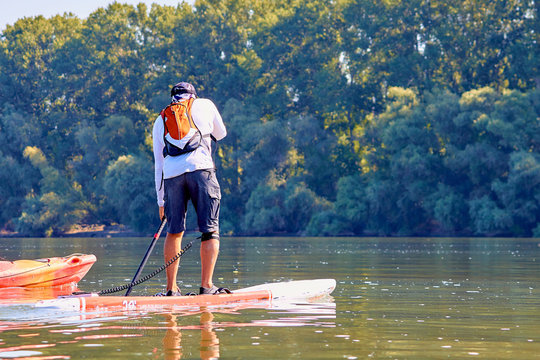 Athletic man paddling on stand up paddle board (paddleboard, SUP) in Danube river at summer