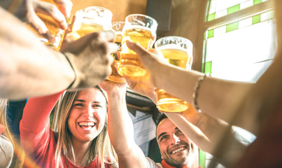 Friends drinking and toasting beer at brewery bar restaurant - Friendship concept on young millenial people having fun together on happy hour at brew pub - Focus on girl face - Summer sunshine filter