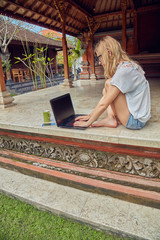 Freelancer girl with smartphone, coffee / tea and laptop on a home porch.