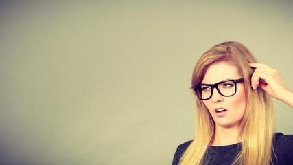 Nerdy woman in eyeglasses being confused