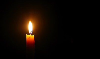 Yellow candle light burn against black background
