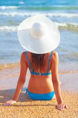 Pretty woman in blue bikini posing on a sea beach