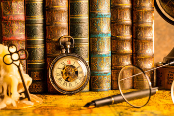 Antique clock on the background of vintage books. Mechanical clockwork on a chain. Fountain pen and glasses. Fototapete