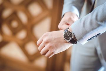 Dressed Man putting his wrist watch