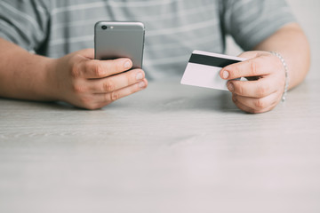 Cropped picture of man with credit card white pattern and phone