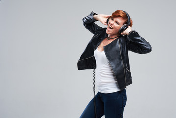 Portrait of a young woman singer with headphones loudly sing a rock song with mouth wide open and with an expression of happiness on her face. Neutral grey studio background