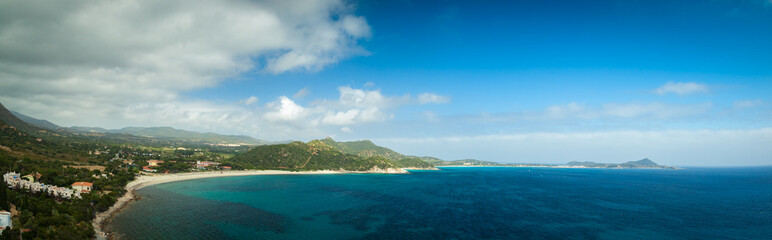 Panoramic aerial view to sandy beach of mediterranean sea with hills and mountains at background. Sardinia, Italy