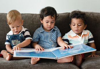 Three little boys reading a book on a sofa