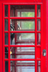 Telephone Booth Door Close Up / Detail of double red vintage english phone box, many small glass windows at door, interior view inside through it (copy space)