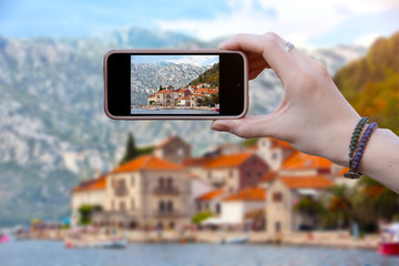 Woman tourist taking pictures on smartphone beautiful view of the city of Perast in Montenegro. Travel concepts and technology. close up