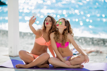 Sexual girl in a bright bikini on a sunny beach. Bikini, red lips, blue sea, tanned girl. Two friends have a rest on the sea, make selfie, use a mobile phone