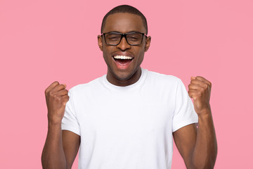 Excited lucky black man feeling winner isolated on pink background
