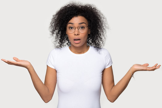 Confused doubtful baffled black woman shrugging looking at camera