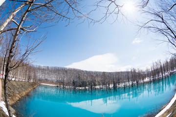 雪が溶け始めた春の湖 美瑛町