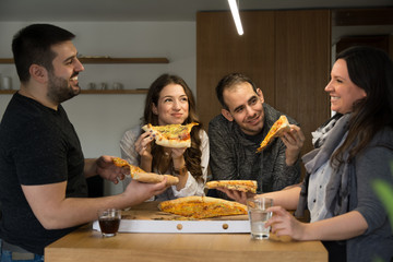 Group of happy young people eating pizza in a modern kitchen