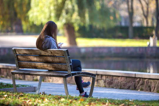 Back view of young girl with long hair sitting on wooden bench in summer park using cellphone on green trees and lake blurred sunny background.