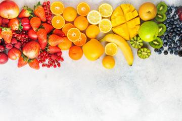 Wall Mural - Rainbow fruits berries background on white. Top view of strawberries blueberries cherries mango apple lemons oranges red currants plums blackberries, selective focus