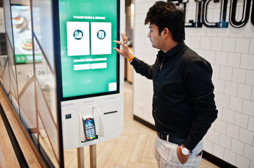 Indian man customer at store place orders and pay through self pay floor kiosk for fast food, payment terminal. Make a choise of language on screen.
