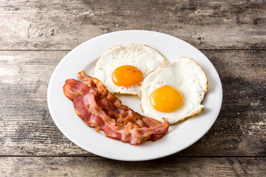 Fried eggs and bacon for breakfast on wooden table