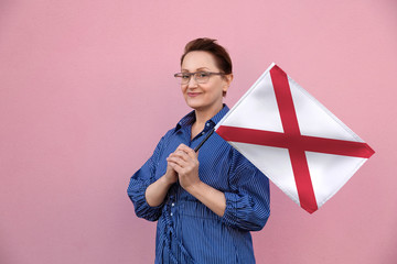 Alabama flag. Woman holding Alabama state flag. Nice portrait of middle aged lady 40 50 years old holding a large state flag over pink wall background on the street outdoor.