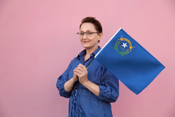 Nevada flag. Woman holding Nevada state flag. Nice portrait of middle aged lady 40 50 years old holding a large state flag over pink wall background on the street outdoor.