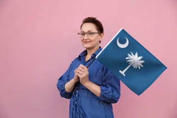 South Carolina flag. Woman holding South Carolina state flag. Nice portrait of middle aged lady 40 50 years old holding a large state flag over pink wall background on the street outdoor.