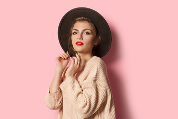 Wall Mural - Portrait of glamour stylish model in beige cozy sweater and trendy hat. Attractive young woman posing on pink background. Modern fashion and autumn concept