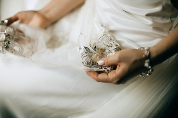 The bride holds a wedding dress with lace in her hands